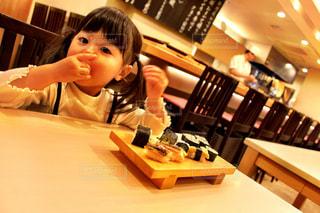 テーブルに座ってお寿司を食べている女の子の写真・画像素材[1643624]