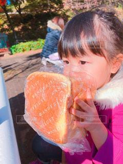 椅子に座ってパンを食べる女の子の写真・画像素材[1643679]