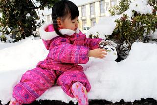 座っている女の子と雪だるまの写真・画像素材[1675697]