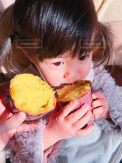 焼き芋を食べる女の子の写真・画像素材[1813852]