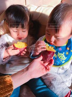 焼き芋を食べる姉弟の写真・画像素材[1813853]