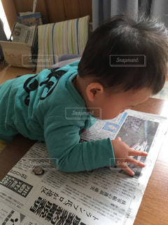 新聞を読む一歳児の写真・画像素材[1569725]