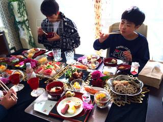 食事のテーブルに座っている人々 のグループの写真・画像素材[1718819]