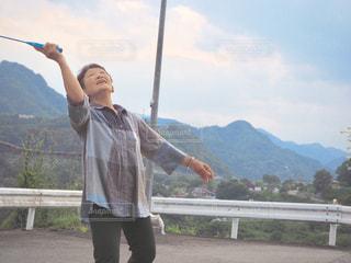 山の前に立っている男の写真・画像素材[1553345]
