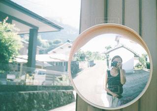 カメラにポーズ鏡の前に立っている人の写真・画像素材[1834394]