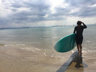 サーフボードを持ってビーチに立っている人の写真・画像素材[1551652]