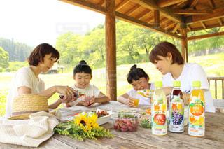 食べ物を食べるテーブルに座っている人々のグループの写真・画像素材[2214400]