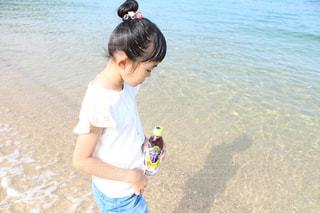 水域の近くの砂の中に立っている小さな男の子の写真・画像素材[2214604]
