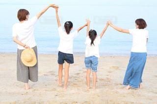 浜辺でフリスビーを演奏する人々のグループの写真・画像素材[2261218]