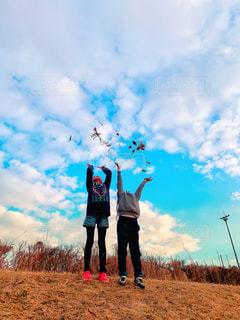 野原に立ちながら凧を持っている人の写真・画像素材[2414521]