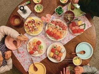 食べ物の皿を持ってテーブルに座っている人々のグループの写真・画像素材[2765287]