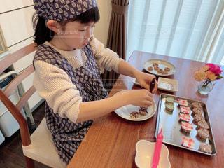 食べ物の皿を持ってテーブルに座っている人の写真・画像素材[2934631]