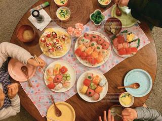 食べ物の皿を持ってテーブルに座っている人々のグループの写真・画像素材[2979850]