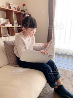 本を読んでベッドの上に座っている人の写真・画像素材[3690249]