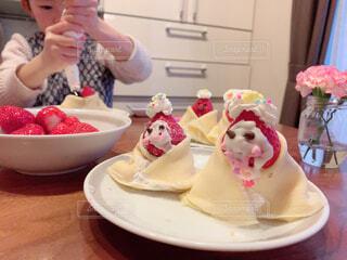 食べ物の皿を持ってテーブルに座っている女性の写真・画像素材[4210440]