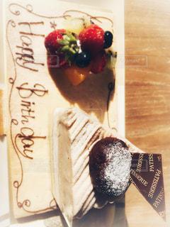 木製テーブルの上に座っているケーキの写真・画像素材[1667708]
