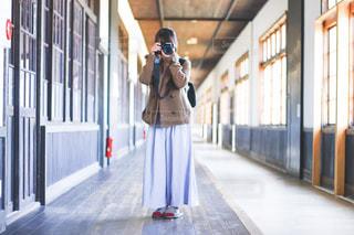 携帯電話で話している建物の前に立っている人の写真・画像素材[1828817]
