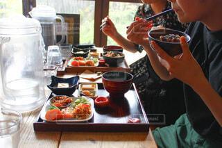 食べ物を食べるテーブルに座っている人の写真・画像素材[3882596]