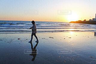 水の体の近くのビーチに立っている男の写真・画像素材[4414846]