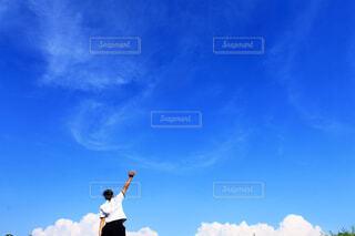 曇りの日に空を飛んでいる男の写真・画像素材[4469690]