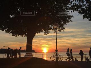 背景の夕日とビーチの上を歩く人々 のグループの写真・画像素材[1698080]