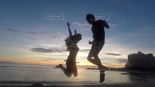 ビーチで空気を通って飛んで男の写真・画像素材[1590840]