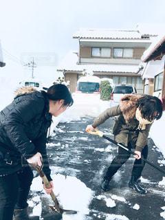 雪かきをする姉妹。の写真・画像素材[1678909]