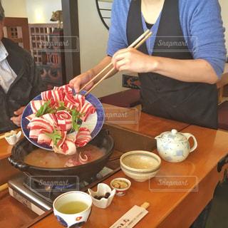 食品のプレートをテーブルに座っている女性の写真・画像素材[1718671]
