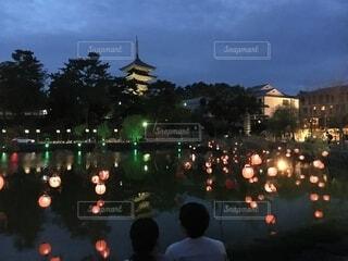 たくさんの提灯が飾られた猿沢池で興福寺の五重塔を見る二人の写真・画像素材[4730845]