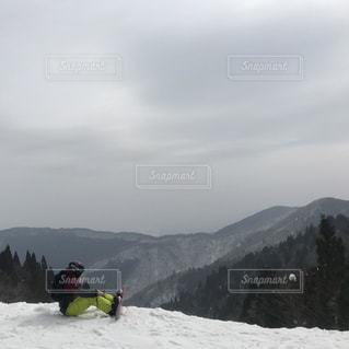 煙る山頂の雪をスノーボードに乗る男の写真・画像素材[1591539]