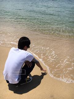 ビーチに座っている男の人の写真・画像素材[1591579]