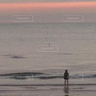 水の体の近くのビーチに立っている人の写真・画像素材[1591591]