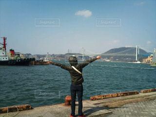 水の体の前に立っている人の写真・画像素材[1591706]