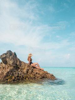 岩場のビーチに立っている男の写真・画像素材[2098020]