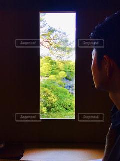 テレビ画面の前に立っている男の写真・画像素材[1601597]