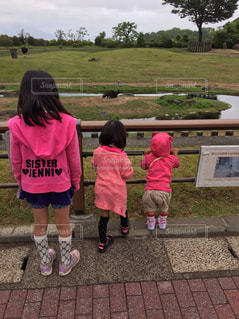 動物園で遠くの動物に話しかける3姉妹の後ろ姿の写真・画像素材[1622914]