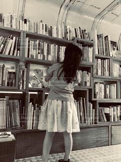 本の棚の前に立っている女の子の写真・画像素材[1590599]