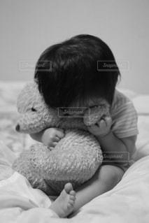 ベッドの上に座ってテディベアを抱きしめる小さな男の子の写真・画像素材[2836774]