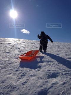 子ども,冬,雪,太陽,白,雲,晴れ,青空,青,男の子,ソリ,日中