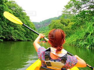 沖縄の西表島でカヌーをする女性の後ろ姿の写真・画像素材[2149845]