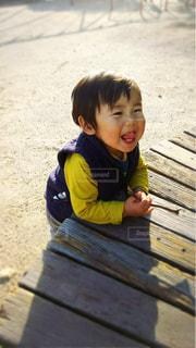木製のベンチに座っている小さな子供の写真・画像素材[1612651]