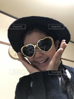 帽子とサングラスのカメラにポーズを身に着けている女性の写真・画像素材[1611653]