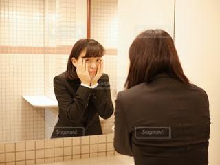 鏡越しにこちらを見る女性の写真・画像素材[1886228]