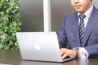 スーツとノート パソコンの前に座ってネクタイを身に着けている男の写真・画像素材[1642910]