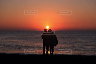 浜辺で、日没の前に立っている人の写真・画像素材[1304868]