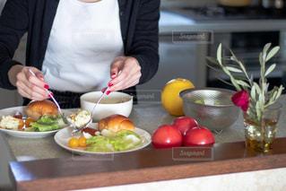 食品のプレートをテーブルに座っている女性の写真・画像素材[1787932]