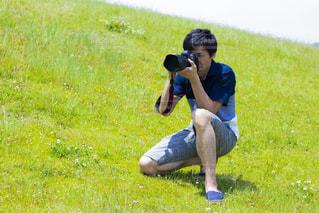 芝生に覆われた野原の上に座る人の写真・画像素材[2169200]