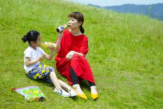 草の上に座っている小さな男の子の写真・画像素材[2215667]