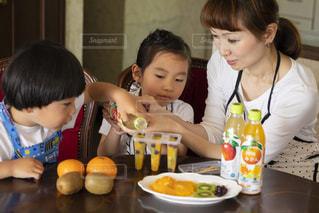食べ物のあるテーブルに座っている小さな女の子の写真・画像素材[2215681]