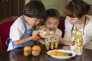 食べ物を食べながらテーブルに座っている小さな男の子の写真・画像素材[2215690]